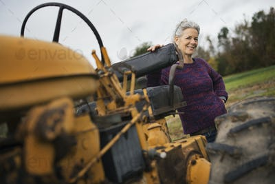 Organic Farmer at Work. A woman by a tractor.