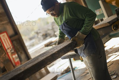 A man examining a large plank of cut wood, in a reclaimed timber yard. A workshop.