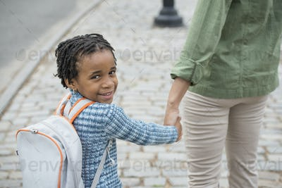 A boy wearing a school bookbag, and walking hand in hand with a woman.