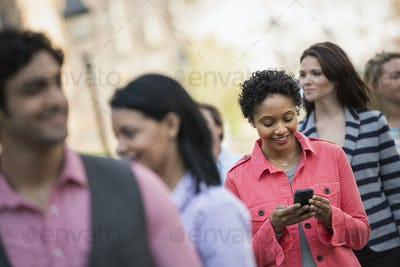 People outdoors in the city in spring time. A woman standing among a group checking her cell phone.