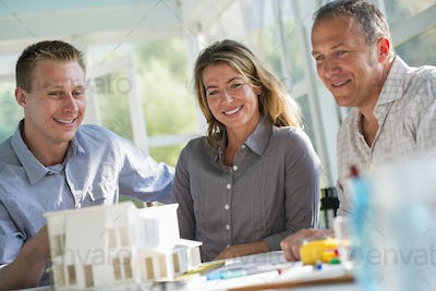 Three people looking at a model of a house on the table.