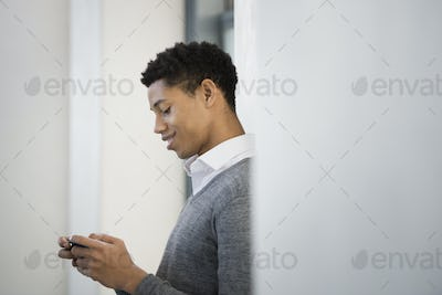 A young man in a grey sweater using his mobile phone.