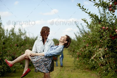 Rows of fruit trees in an organic orchard. Two young women laughing, one carrying the other.