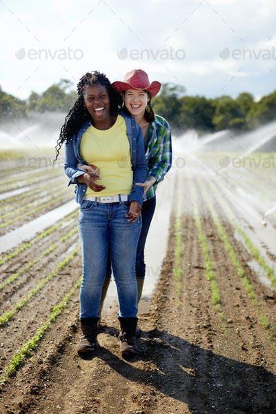 Two young women standing in a field of small seedlings, with the irrigation sprinklers spraying.