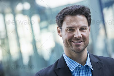Business people in the city. A  man in a blue shirt and dark jacket smiling.