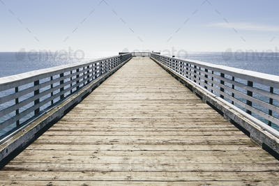 A long pier with railings extending out over the Pacific Ocean leading to the horizon.