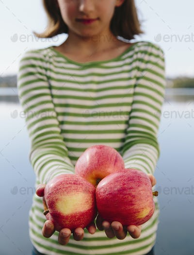 Nine year old girl holding handful of organic apples