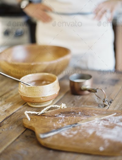 A domestic kitchen. A cook preparing a meal. A large bowl with oill and flour. Creating pastry.