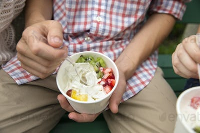 Young people sitting side by side, eating fresh organic fruit and yoghurt desert.