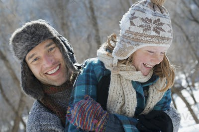 A young girl with a bobble hat and scarf and a man hugging her wearing winter clothes.
