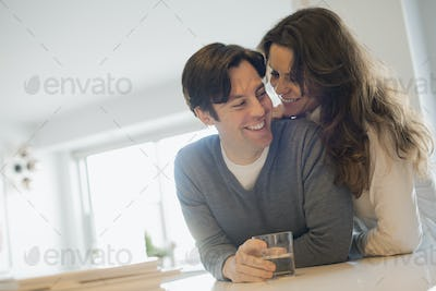 Couple connecting at home in kitchen