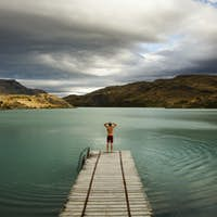 A young man standing at the end of a wooden pier on a lake in Torres del Paine National Park, Chile.
