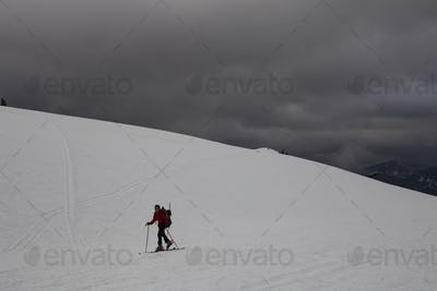 A skier skins or traverses up a snow field as dark clouds gather on Mount Baker, Washington, USA.