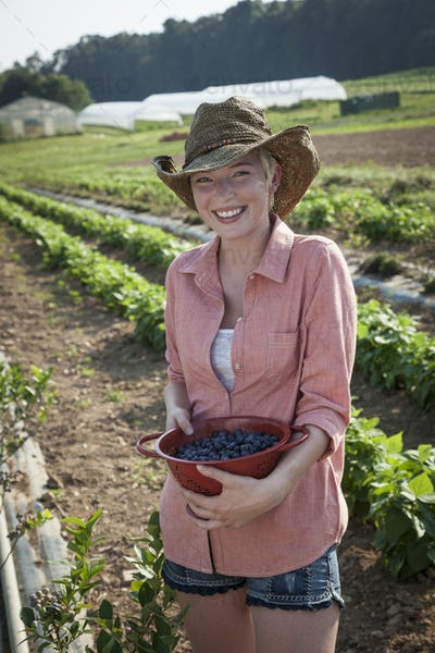 A girl in a pink shirt holding a large bowl of harvested blueberry fruits.