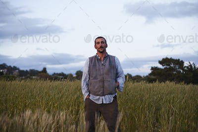 A man standing by a field of growing cereal crop, at the Homeless Garden Project in Santa Cruz.