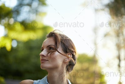 A young woman in the woods at dusk.