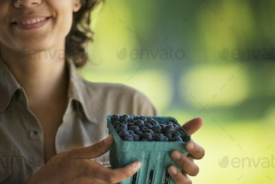 A woman with a punnet of fresh picked blueberries or soft fruit.