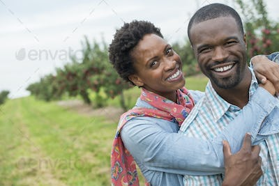 An organic apple tree orchard. A couple hugging and smiling at the camera.