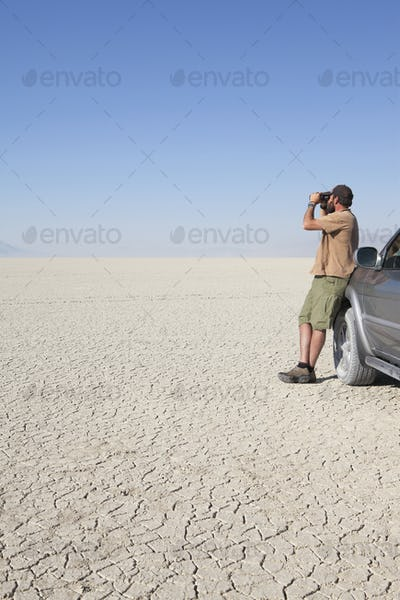 A man standing in a dry desert, looking through binoculars and leaning against a truck