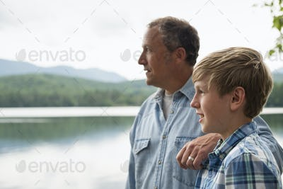 A family outdoors under the trees on a lake shore. Father and son.