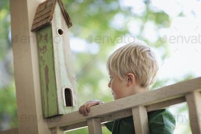 A child examining a bug box on a porch.