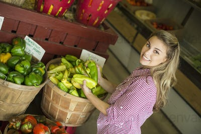 A young blonde haired woman sorting different types of bell pepper for sale in a store.