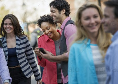 A group of men and women in the city, two looking at a cell phone screen and laughing.