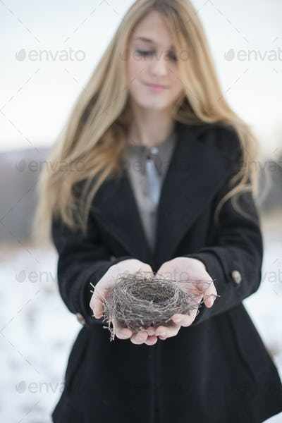 A young woman holding an old bird's nest in her hands, tightly woven twigs. Winter scene.