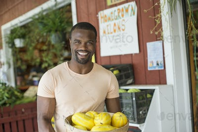 A man carrying a large basket of yellow squash vegetables. Displays of fresh produce for sale.