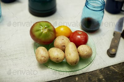 A table with a cloth, and plate with potatoes and tomatoes.