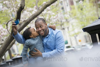 A New York city park in the spring. A father and son side by side taking selfie with smart phone.