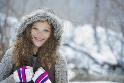 Winter scenery with snow on the ground. A young girl in a woolly hat with ski gloves on.