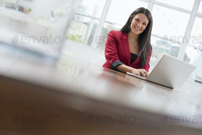 A young woman sitting comfortably in a quiet airy office environment. Using a laptop.