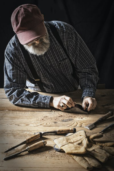 A man working in a reclaimed lumber yard workshop, sanding knotted piece of wood.