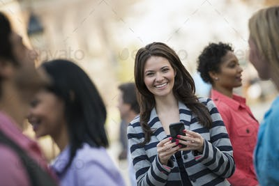 People outdoors in a New York City park. A woman holding a mobile phone, looking at the camera.