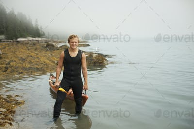 A man in a wetsuit drawing his kayak onto the shore, in misty weather.  New York State, USA
