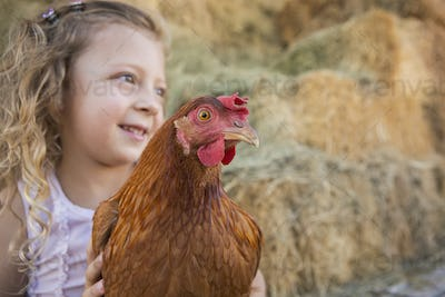 A young girl holding a chicken in a henhouse.