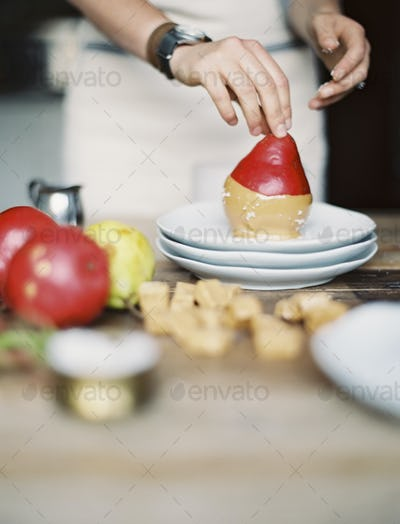 A woman in a domestic kitchen making fresh pear dessert.