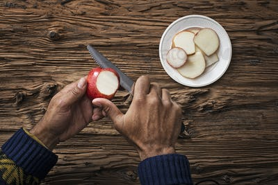 A person holding and slicing sections of a red skinned apple.