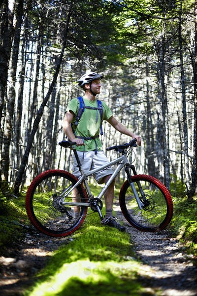 A mountain biker in a helmet with a rucksack standing by his bicycle in woodland.