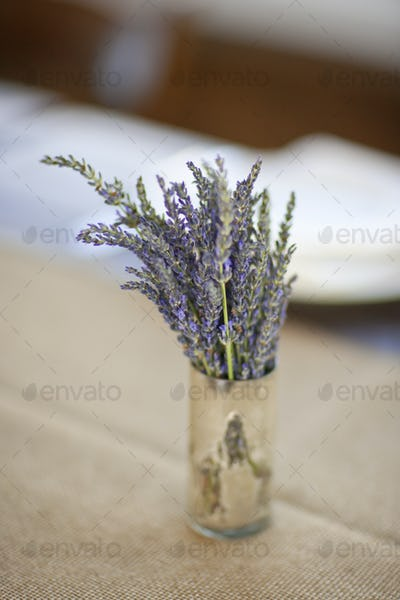 A small pot with fresh lavender flowers on a table top.