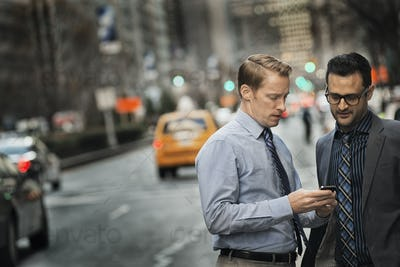 Two men standing together looking at a cell phone display on a busy street at dusk.