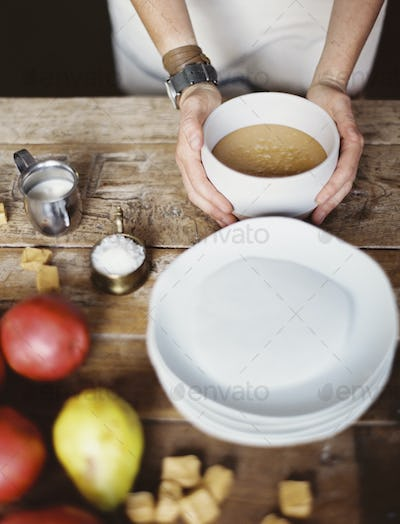 A domestic kitchen tabletop with pears and bowl of fudge sauce.