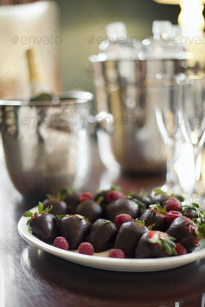 Plate of hand-dipped chocolate strawberries, champagne and glasses.