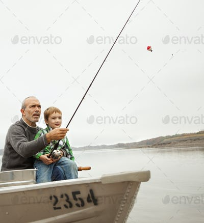 A day out at Ashokan lake. A man showing a young boy how to fish, sitting in a  boat.