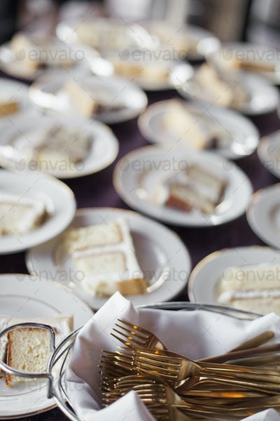 A table laden with plates. White china, and a basket full of dessert forks. A slice of wedding cake.