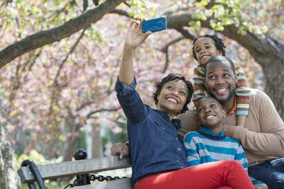 A New York city park in the spring. A woman taking a family selfie with a smart phone.