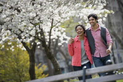 People outdoors in the city in spring time. New York City park. A man and woman side by side.