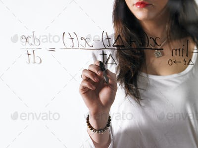 A young woman writing a mathematical equation with black marker on a clear seethrough surface.