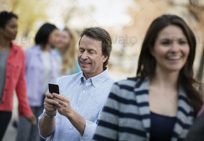 People outdoors in the city in spring time. A man checking his cell phone, among a group.